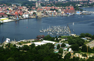 Im Vordergrund ist ein Teil des aufgespülten Dänholms zu sehen, wo auch ein Yachthafen untergebracht ist. Im HIntergrund Stralsund.