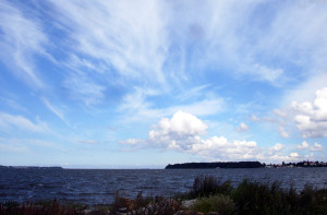 Der nördliche Dänholm ist ein beliebter Aussichtsort. In der Ferne liegt die INsel Hiddensee, deren Leuchtturm bei klarer Sicht gut zu erkennen ist. Rechts das beschauliche Fischerdorf Altefähr.